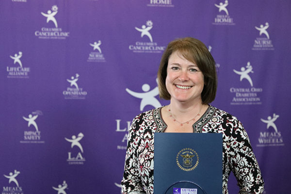Kelly Hollis poses with the Outstanding Spirit Award at the LifeCare Alliance Volunteer Recognition event on Monday, April 30, 2018. Photo by Andrew Zuk, LifeCare Alliance.
