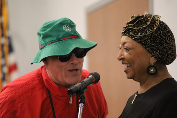 A mystery man visits emcee Sandi Taylor at the Spring Style Show at LifeCare Alliance on Wednesday, June 6, 2018.
