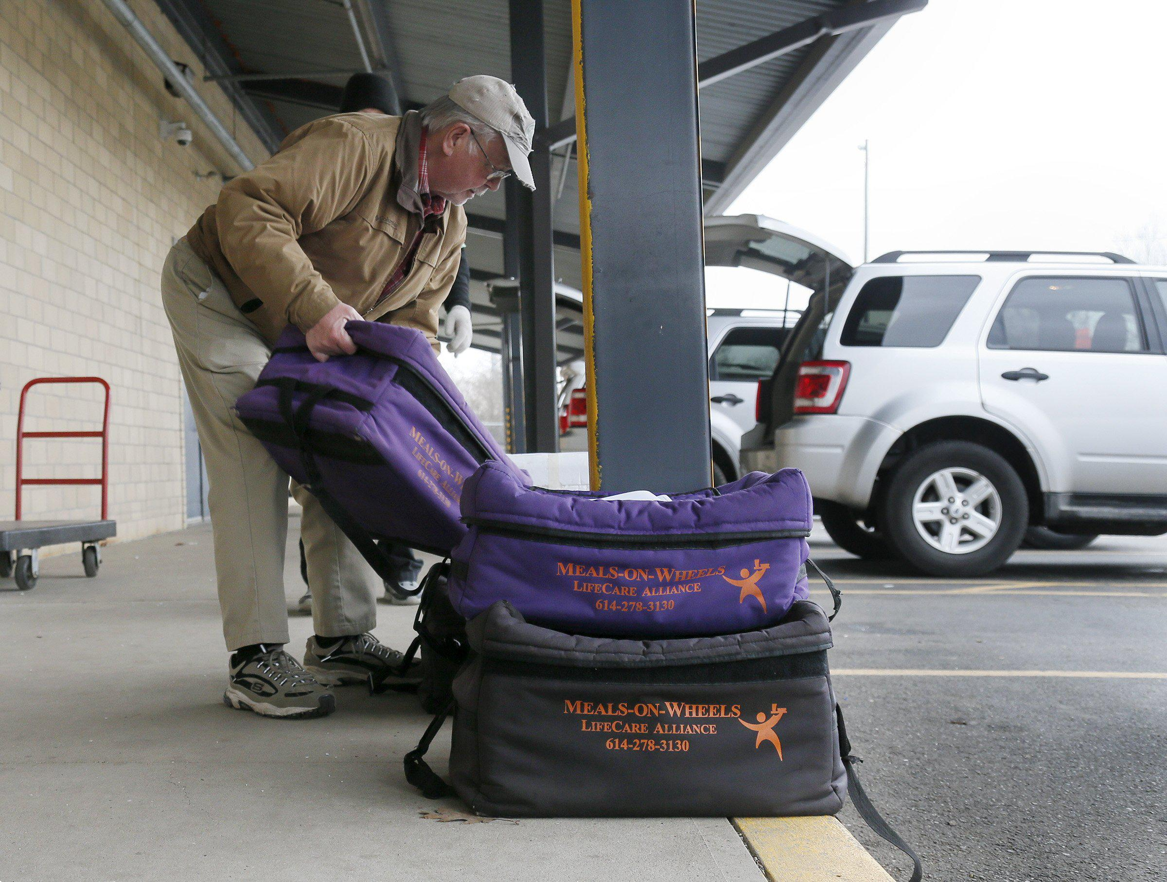 Volunteer Bill Abbott loads Meals-on-Wheels delivery bags into his vehicle.