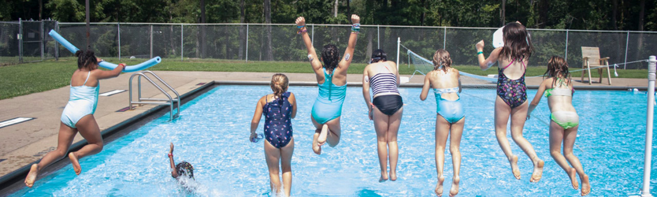 Campers jumping into a pool together