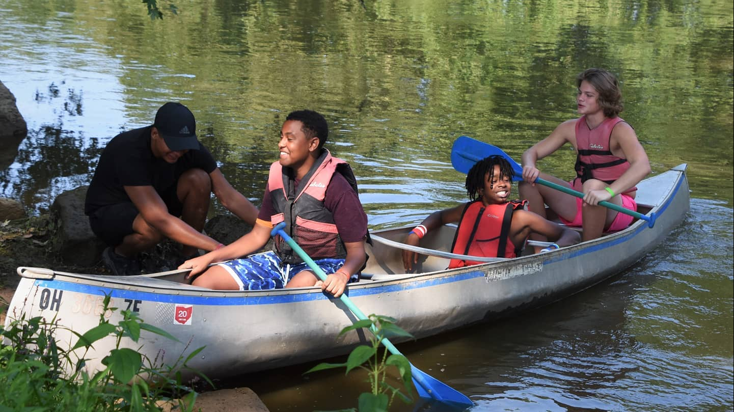 Three teenage male campers in a canoe at Camp Hamwi